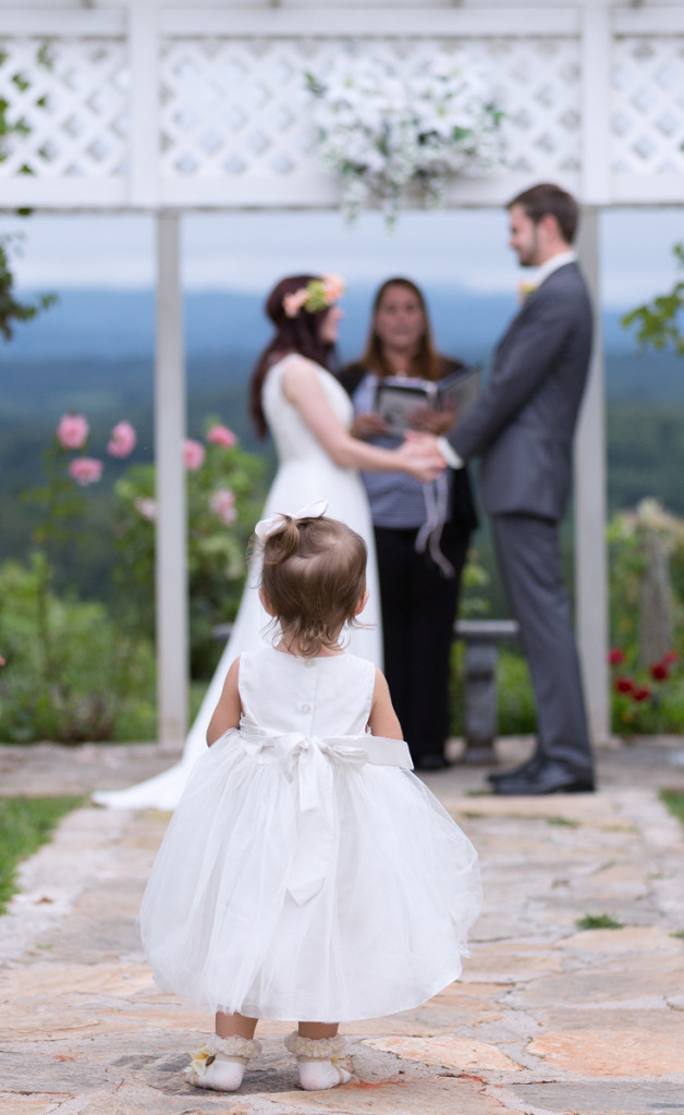 Image by Asheville Wedding Photographers - Forge Mountain Photographey. Young child standing in the aisle  as the ceremony takes places looking out into the Blue Ridge Mountains.