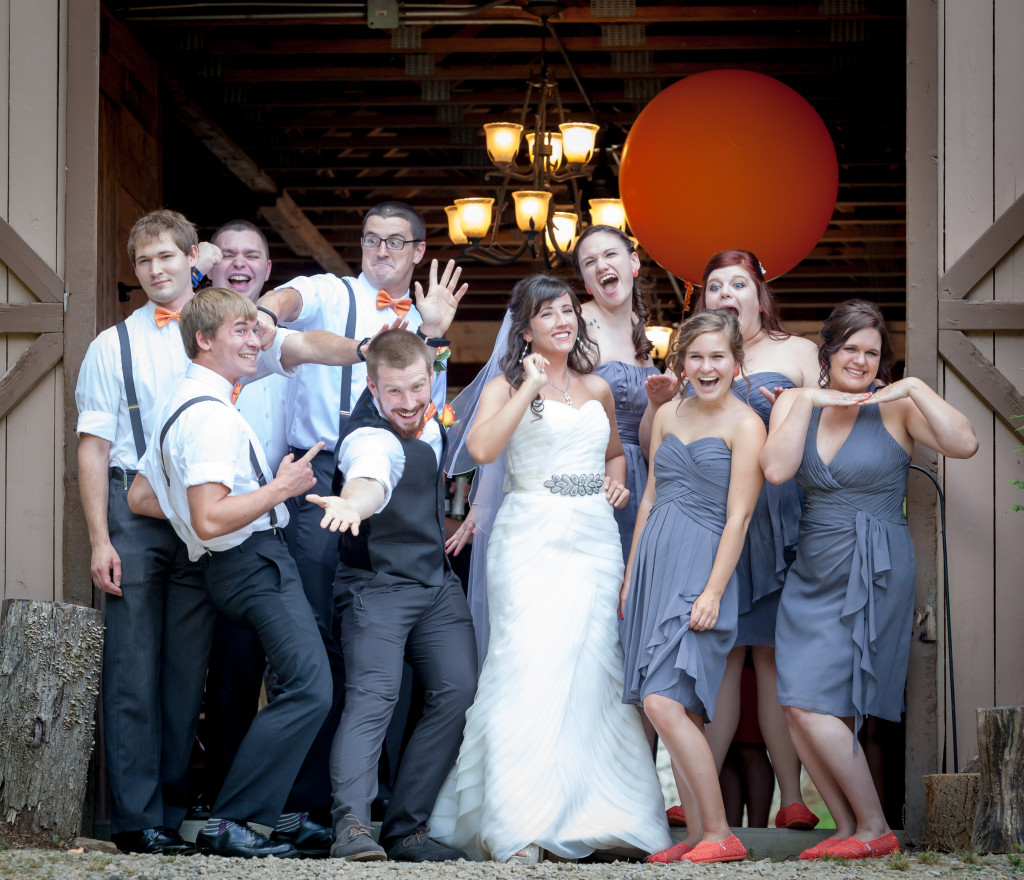 Large barn with wedding party standing in the door. The wedding party is taking a formal, whoever everyone is strike a silly pose! Asheville Wedding Photographer Will Thomas provided the photo.