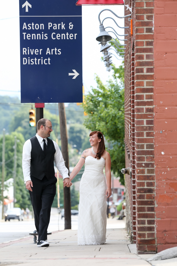 Bride and Groom walking up Biltmore Ave in Asheville holding hands.