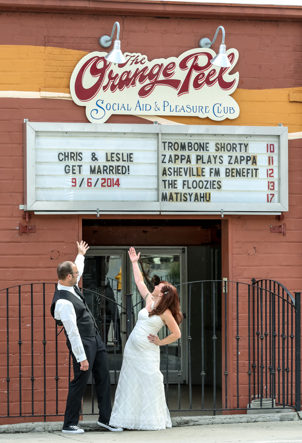 Bride and Groom under The Orange Peel sign pointing to their names listed on the sign.