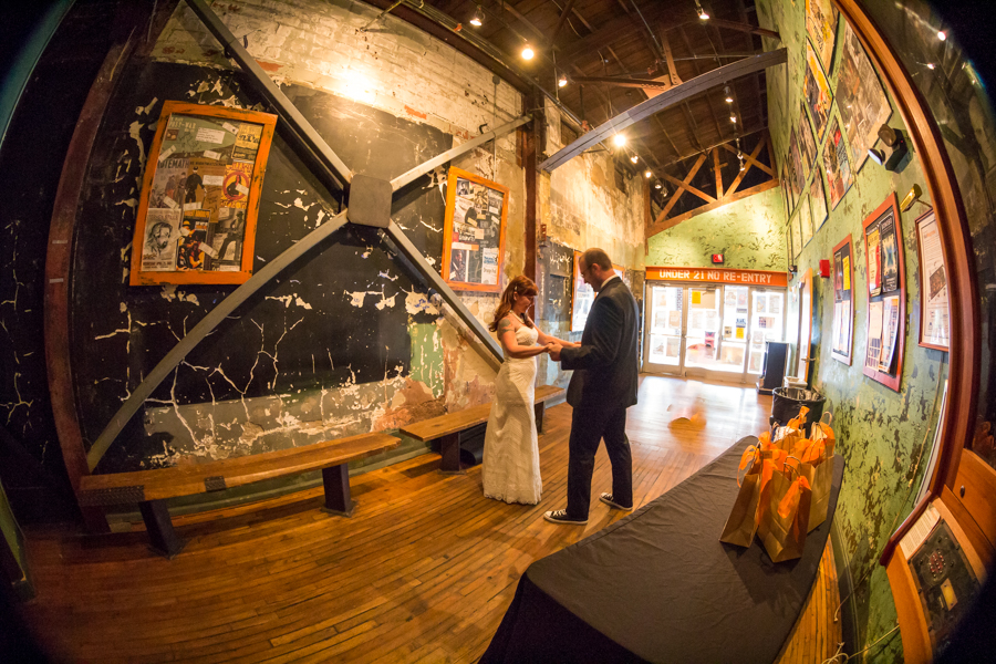 Bride and Groom standing in the doorway at the Orange Peel holding hands.
