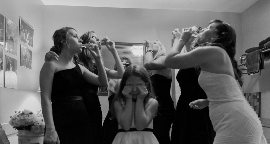 Bridal party taking shots while a young girl puts her hands over her eyes.