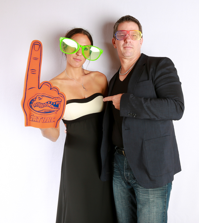 Couple in the Photo Booth both wearing funny glasses and one holding a large gators fan number one . Both couples are wearing black.