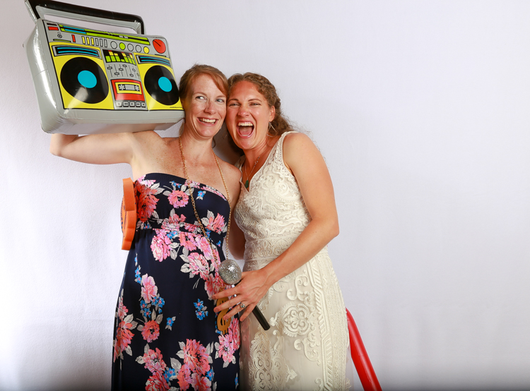 Bride and pregnant woman in the Photo Booth one with the inflatable pony the other with a boombox