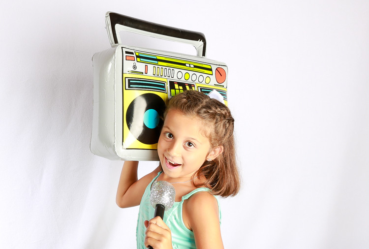 Young girl in wedding photo booth holding a microphone and a huge boombox