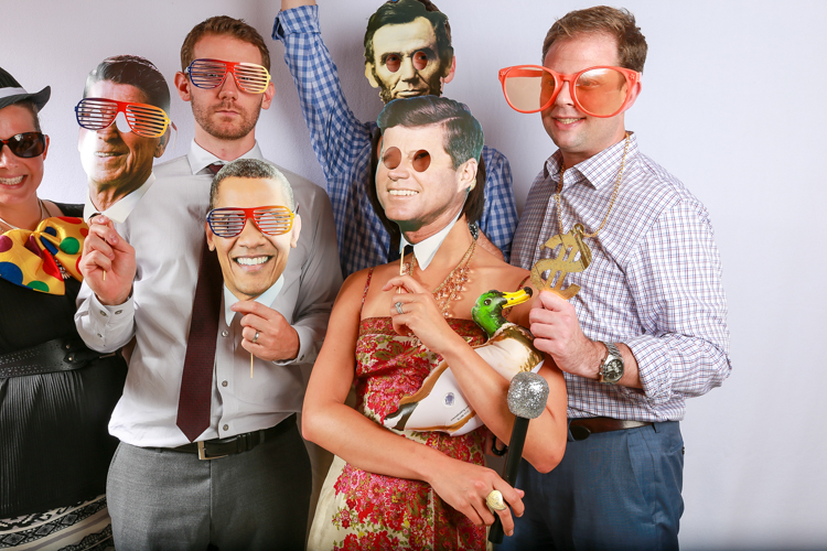 Large group of people and photo booth where presidential mask and funny glasses