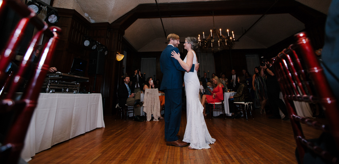 A full body view of bride & groom having first dance.
