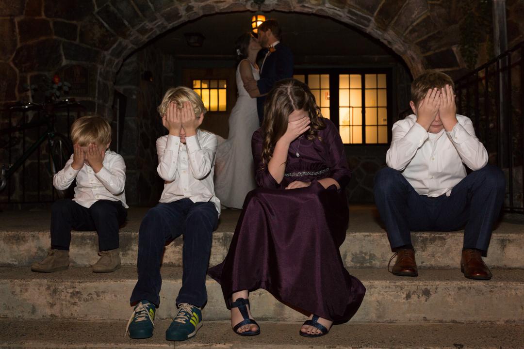 4 kids covering their eyes as bride & groom kiss behind them