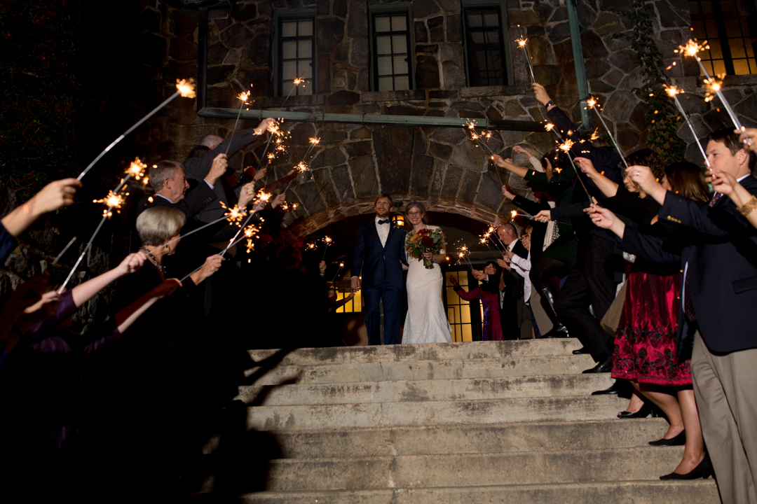 Kerry & Heather stand at top of stairs as everyone is lined on both sides with sparklers