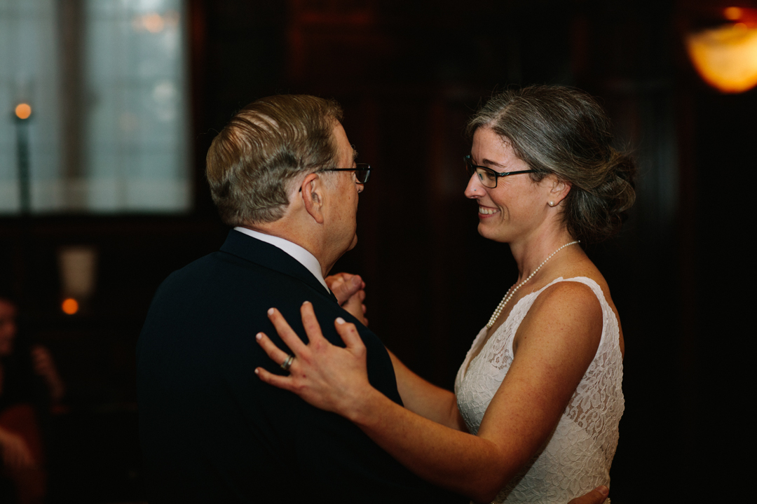 Heather with huge smile looking at father as they dance