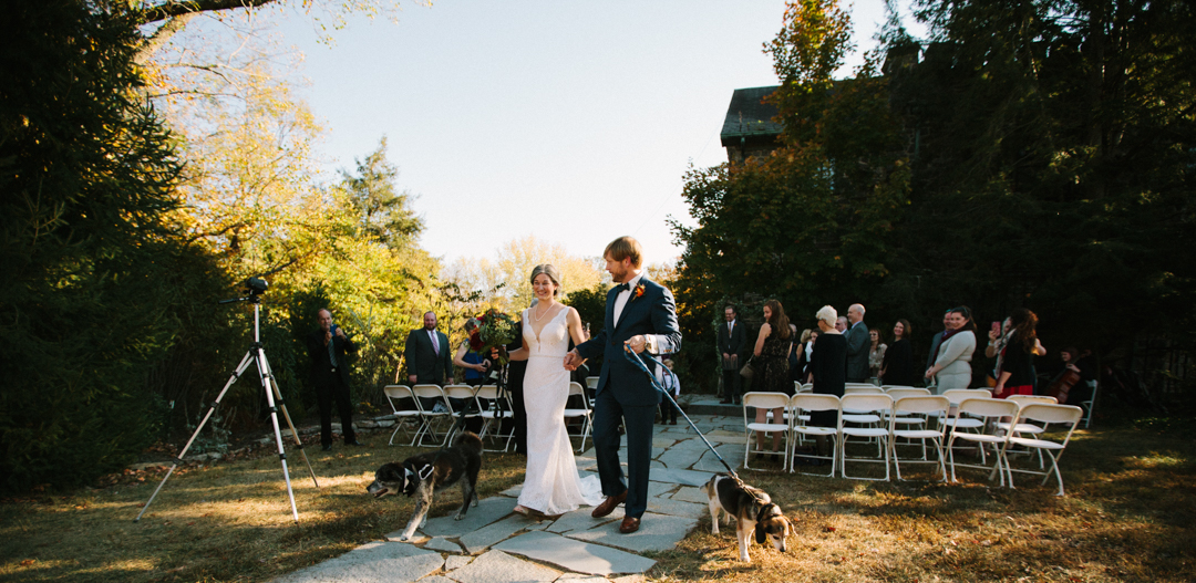 Heather and Kerry holding hands walking down aisle with dogs on leashes