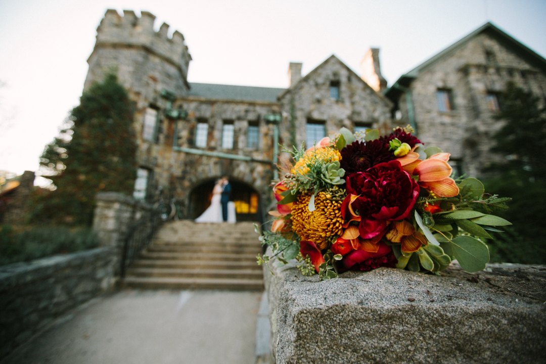 Bouquet in focus on a stone wall with the Homewood castle and bride and groom kissing on steps