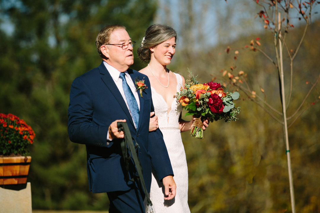 Sun is shining bright on the faces of the bride and her father as they confidently walk down the aisle