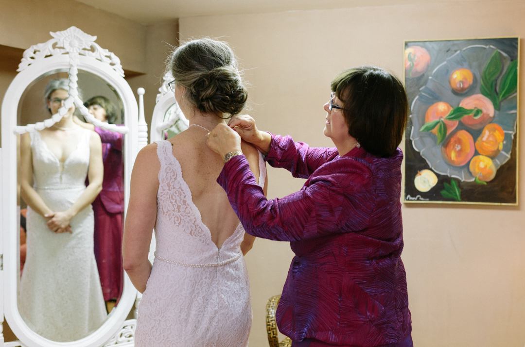 Picture of Heater looking into a mirror as her mother clasp her necklace. She is in her wedding dress.