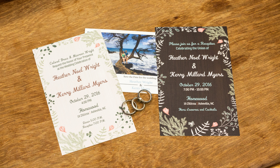 Wedding invitations with engagement and wedding rings on wooden board