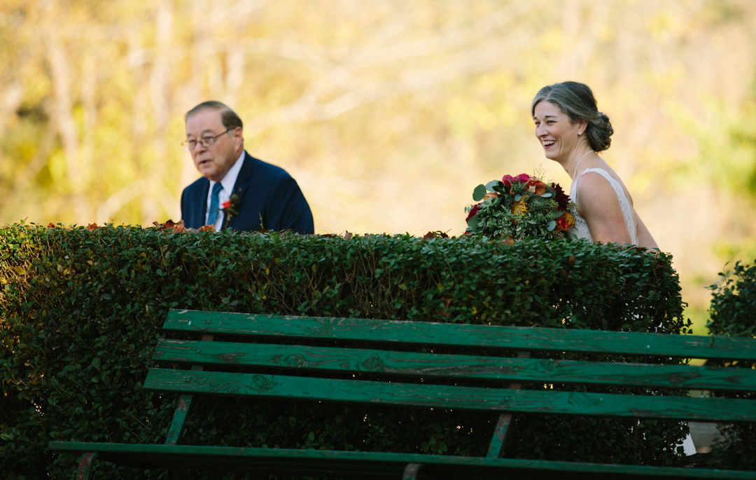 Bride with father about to walk down aisle but laughing at the ring bearer who is goofing off.