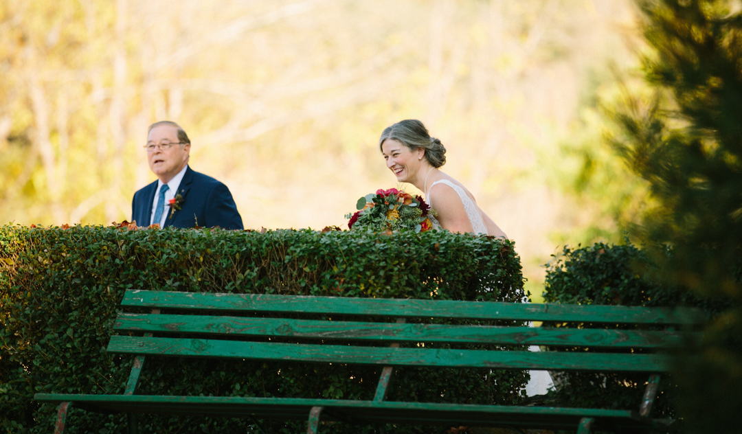 Heather and her father looking over the hedges as the ring bearer her nephew is being a goober