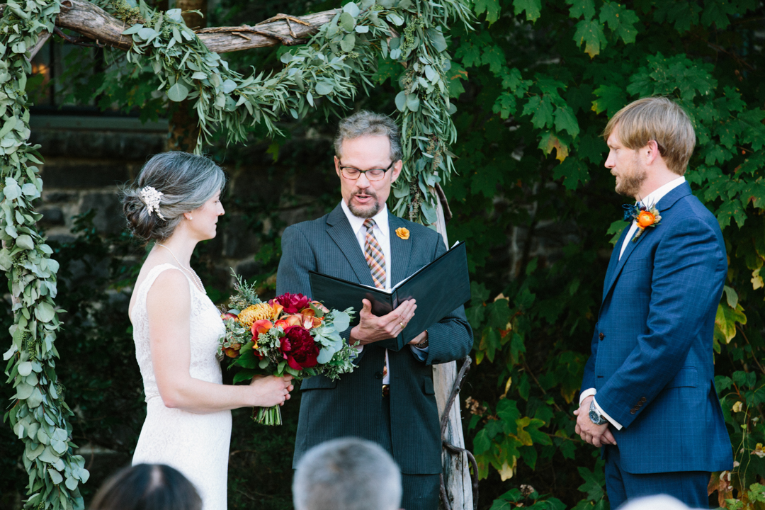 Heather holding her large bouquet listening along with Kerry at the words the minister is saying