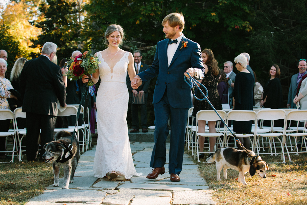 The wedding couple walk back down aisle holding hands with each dog in the other hands celebrating just getting married.