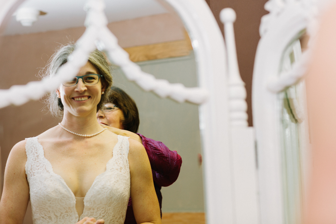 A view of Heather looking into the mirror as her mother helps her button the wedding dress