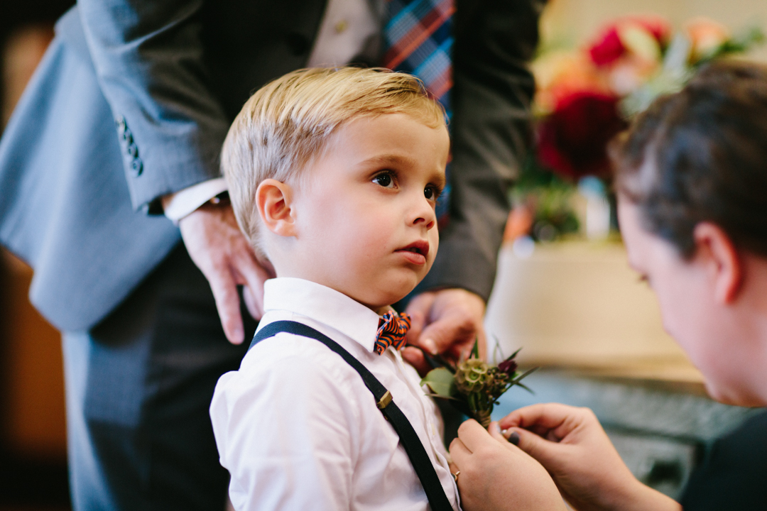 Pinning the boutonniere on the ring-bearer who is Heather nephew