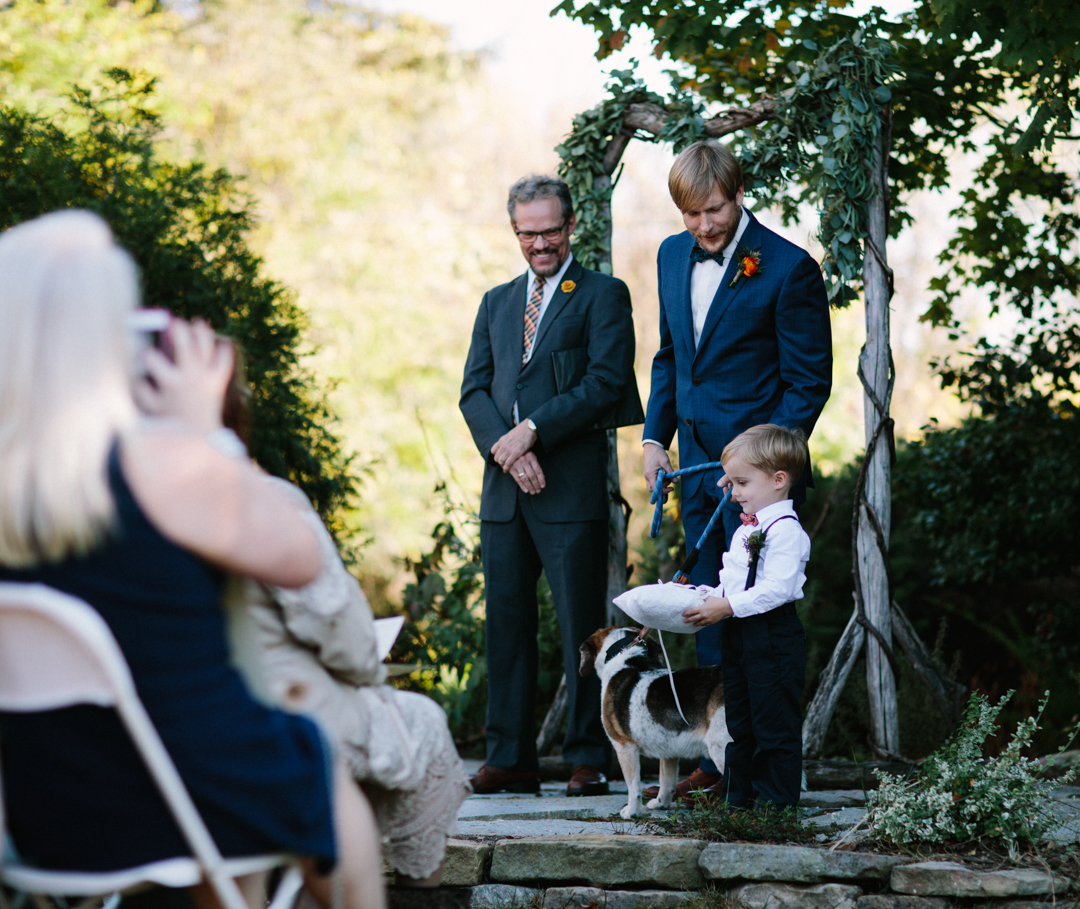 Groom at the front waiting for Bride to come down aisle while checking in with the ring bearer standing next to him