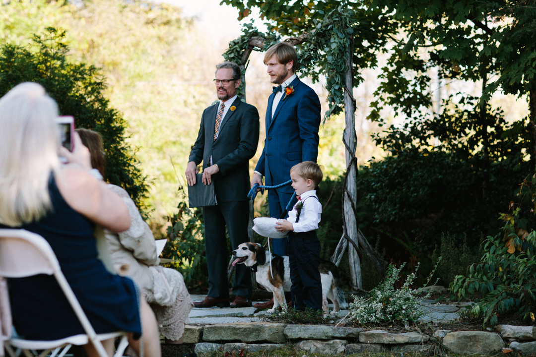 Minister, groom, ring bearer, old dog waiting at the front for the bride to walk down the aisle