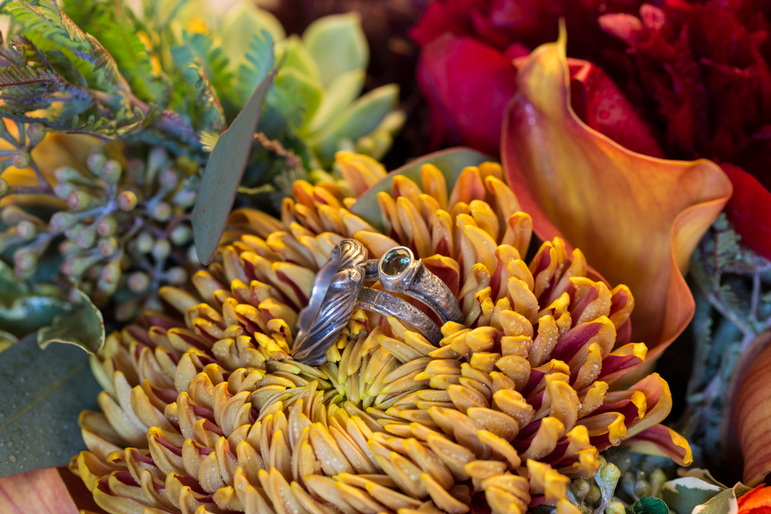 Close up of the wedding bands and engagement ring in flowers.