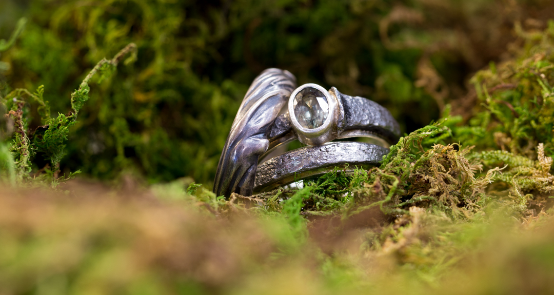 I picture of the wedding rings in green moss.