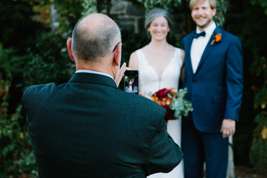 Bride & groom stand at alter after ceremony while family take pictures with their phones