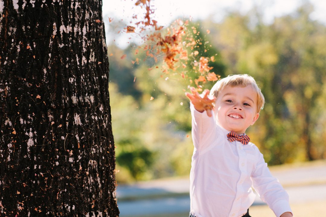 Young ring bearer boy throwing leaves at photographer