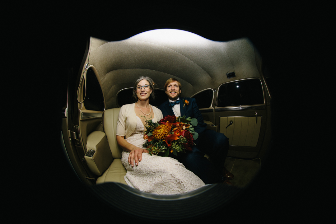 Bride and groom in the classic car leaving the wedding