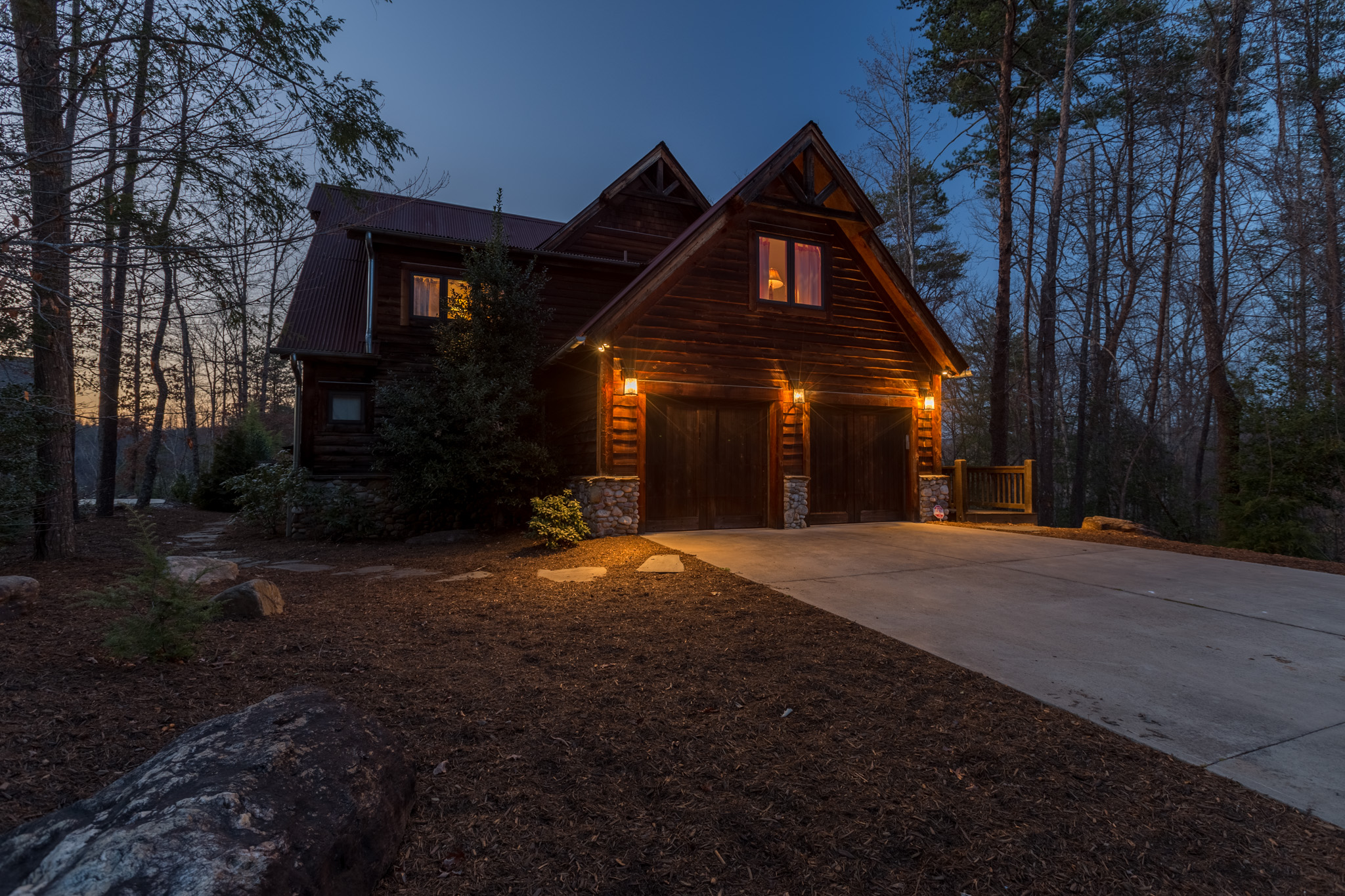 Front view of cabin on Lake James shot at night. Lights are causing a warm glow and looks very inviting