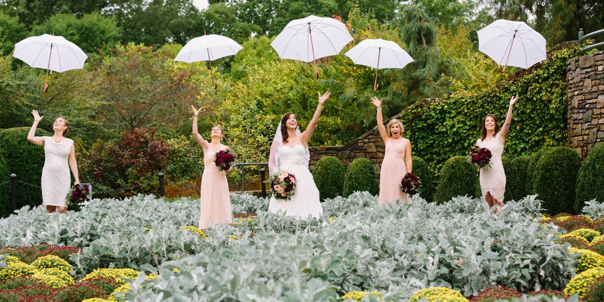 Asheville Wedding Photographer - Bride and Bridesmaid in the rain throwing up their umbrellas to get a picture