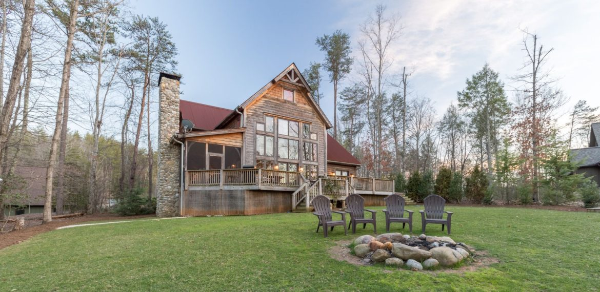 View of seating area around the fire pit with cabin in the background on Lake James best real estate photographer