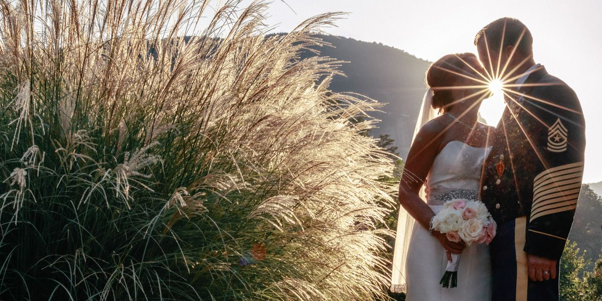 Lake Lure Wedding Photographer - Bride and Groom embrace as star effect from sun is created near their mouth