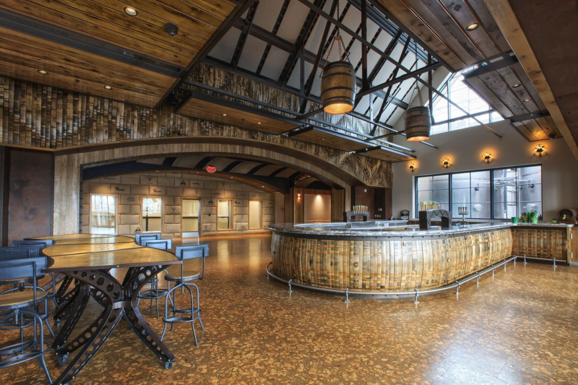 Commercial Photography of Sierra Nevada Brewery in Mills River , NC . Large bar in middle of the room with 2 large barrels as the lighting hanging above the bar.