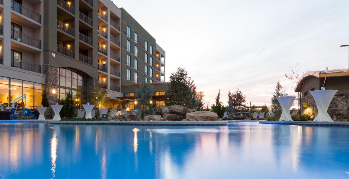 Commerical hotel photography of the pool area of Courtyard by Marriott in Pigeon Forge TN. The image is of the evening hours at pool level with white covered standing tables on the outskirts of the pool