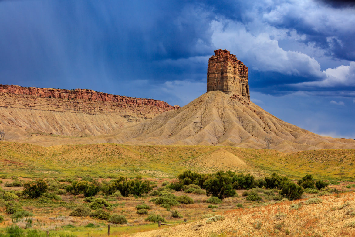 Landscape photography in Ute Chimney Rock. Desert landscape with a few trees back dropped by a bright blue sky with rain in the distance.