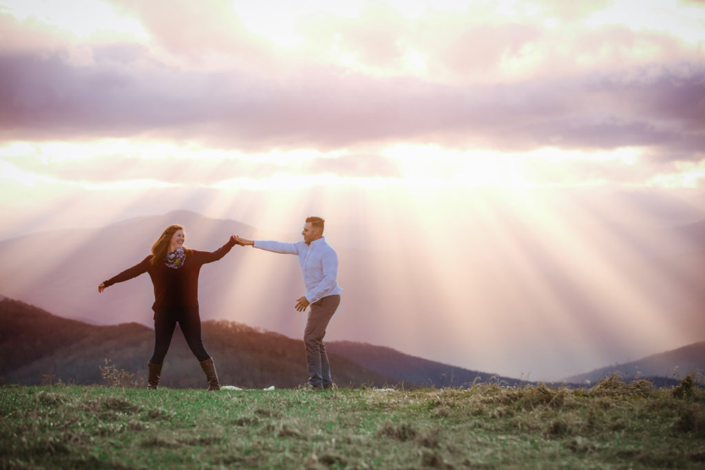 Marissa and Chris dancing on top of Max Patch. You can see mountains in the background as sunrays peak through the clouds. The sun is near setting so the colors in the sky are amazing!