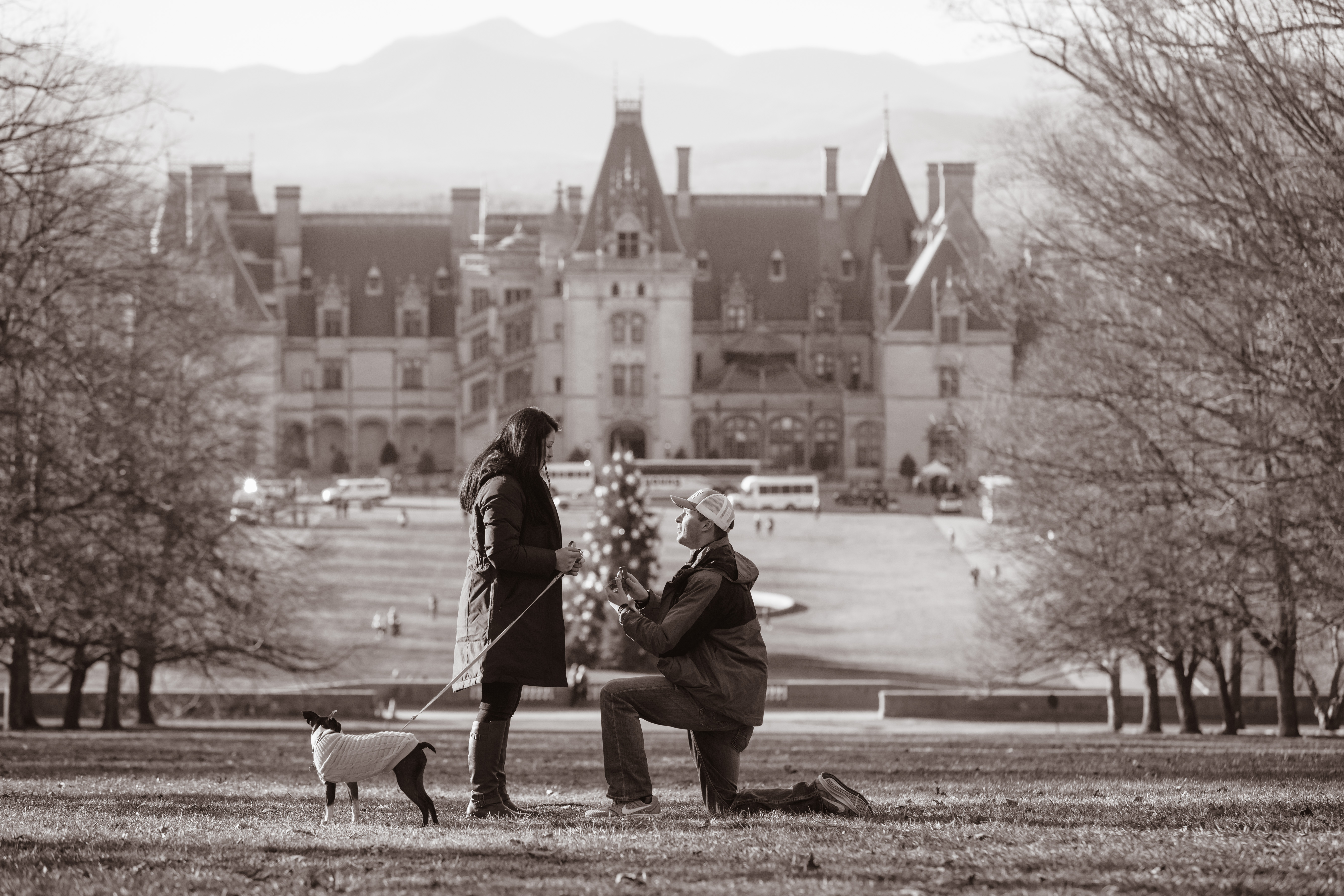 "Taylor Shirley on one knee surprising his girlfriend by proposing on Diana Hill at the Biltmore Estate in Asheville NC. The couple are in front with Taylor holding box holding the engagement ring asking her ""Will you marry me"". The Biltmore and Blue Ridge Mountains are in the background."