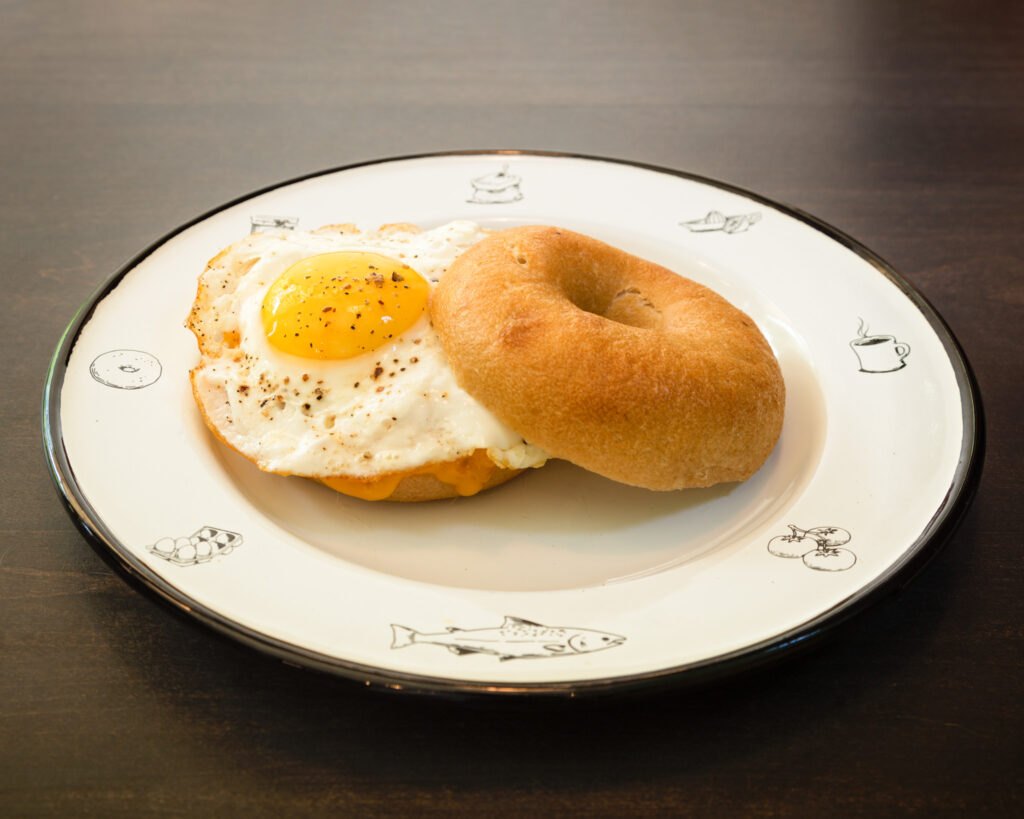 """Egg sunnyside up on a plain bagel sliced in half plated on a nice white plate with a black rim. The plate is decorated on the edges with bagels, eggs, and fish.  The sunnyside up egg has course ground pepper, and you can see cheese starting to peak threw under it. The top of the bagel is most to the side, and just enough is touching the other bagel. According to the decription the ham is """"thinly sliced country ham aged 18 months"""" however you cannot see the ham as it is covered by egg and Ashe County cheddar cheese."""