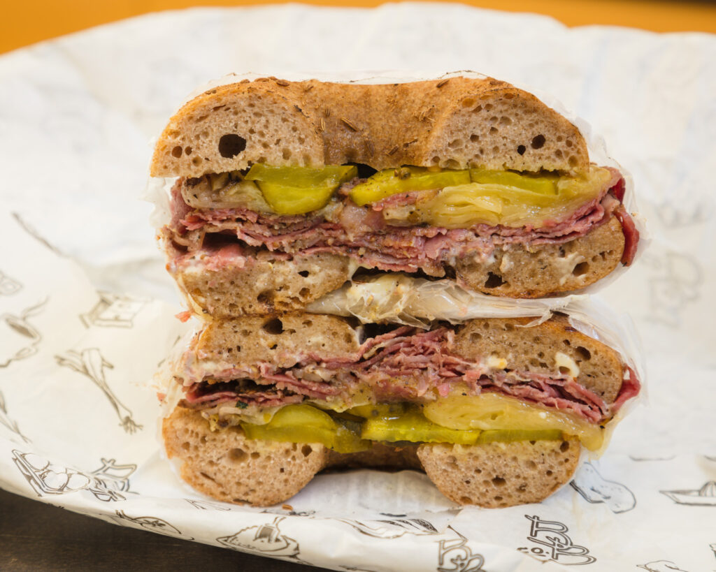 Pastrami on Rye bagel sitting on the table surrounded by white paper.  It has the following on a Rye Bagel - Apple Brandy brisket, Hickory Grove cheese, b&b pickles, Lusty Monk mayo