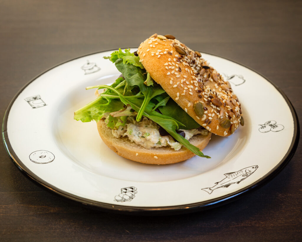 Smoked Chicken Salad Bagel plated on an elegant white plate with a gold rim. The bagel is a seeded bagel and has the following celery, red onions, arugula, and smoked Joyce Farms chicken. The arugula is overflowing from the bagel.