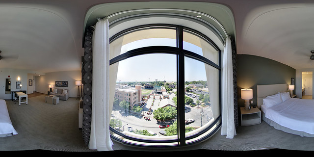 360 image taken from a virtual tour of the a suite at the Hilton in downtown greenville. It is looking out of a very large window overlooking the local baseball teams field.