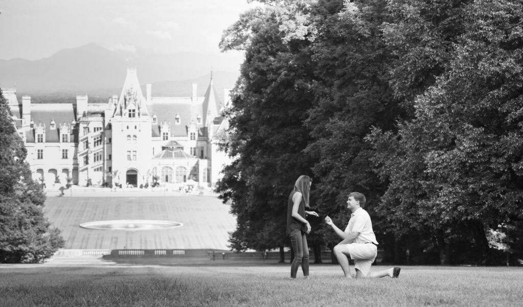 Black and white version of Terry down on one knee proposing with the Biltmore House in the background.  The grass has nice leading lines!