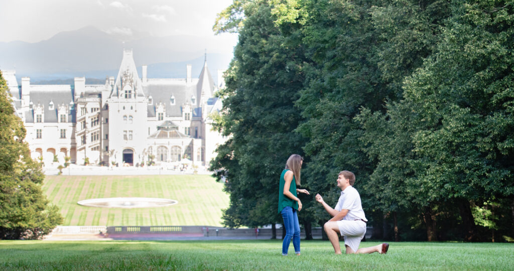 Terry is down on one knee proposing with the Biltmore House in the background.  The grass has nice leading lines! This is the actual surprise proposal on Diana Hill.
