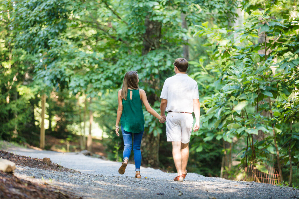 Terry and his bride walking down the path to the next area. It is a gravel path lined with trees.