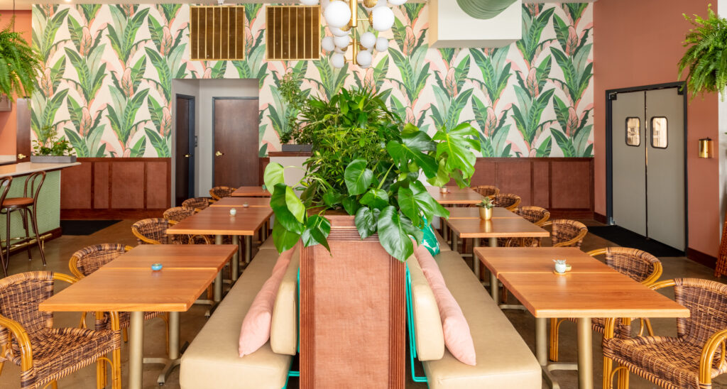 View straight down the center of the bar dining area. Lush green plants create a barrier between guest.