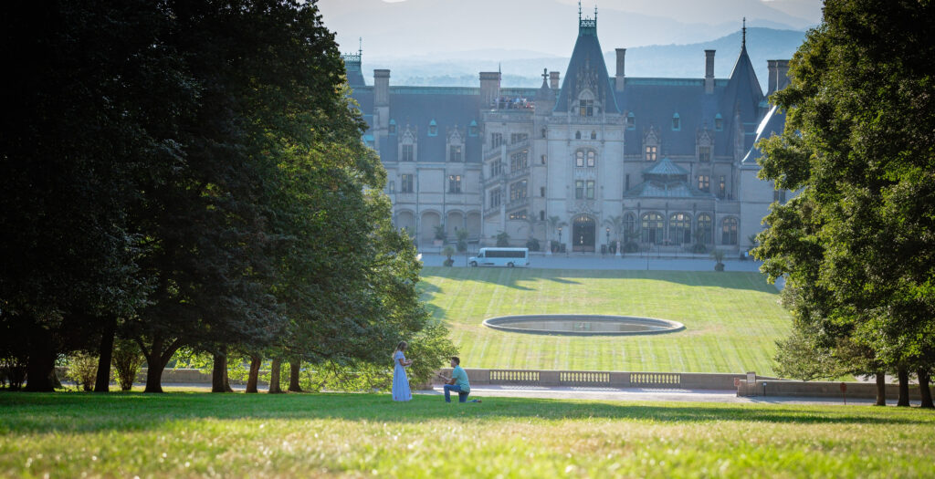 Gage taking a knee in front of the Biltmore House to propose. The view is from the top of Diana Hill with the house in the background.